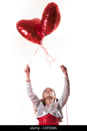 Happy girl holding heart shaped balloons Banque D'Images