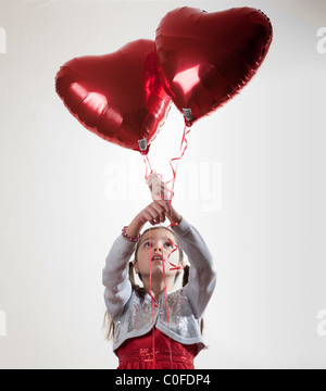 Happy girl holding a heart shaped balloon Banque D'Images
