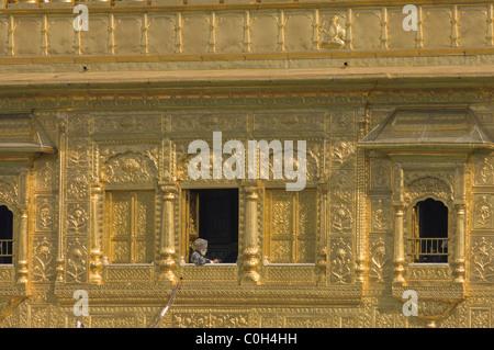 Pilgrim la lecture dans une fenêtre de l'Hari Mandir (Temple divin), le Golden Temple d'Amritsar, Punjab, India Banque D'Images