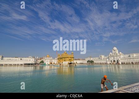 Pèlerin Sikh se baigner dans la piscine de Sarovar (Holy Nectar immortel), avec l'Hari Mandir (Temple) divine derrière, Banque D'Images