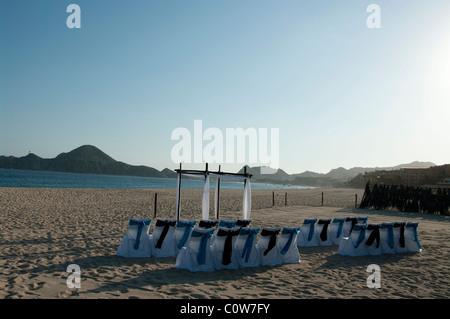 Chaises et d'une arche de mariage mis en place sur une plage en attente pour les invités et les mariés arrivent. Banque D'Images