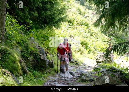 Mère et fille à marcher le long du chemin de montagne dans les Alpes françaises. Banque D'Images