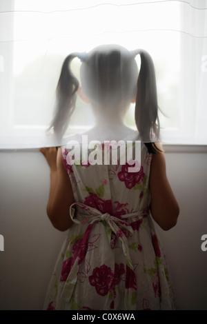 Fille regarde par la fenêtre de derrière rideau Banque D'Images
