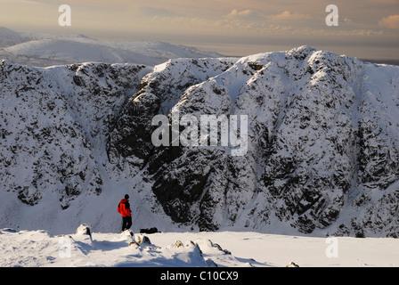 Walker en veste rouge à l'égard de Dow Crag Coniston le vieil homme en hiver dans le Lake District Banque D'Images