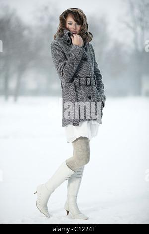 Portrait d'une jeune femme dans la neige, sa main tenant son collier manteau Banque D'Images