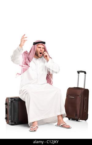 Un furieux cris arabes sur un téléphone mobile assis sur son assurance Banque D'Images