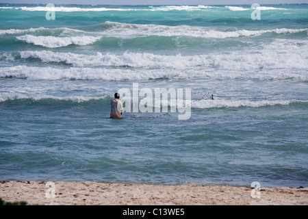La pêche dans les vagues. Un jeune homme utilise un filet jeté pour capturer les poissons juste à côté de la plage Banque D'Images