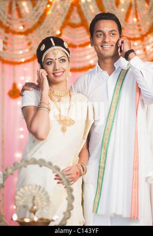 La jeune mariée et le jeune marié en robe traditionnelle d'Inde du Sud talking on mobile phones Banque D'Images