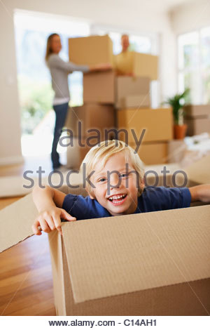 Smiling boy playing sur box in new house Banque D'Images