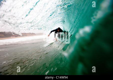 Un surfeur mâle tire dans un tonneau en surfant à Zuma beach à Malibu, en Californie. Banque D'Images