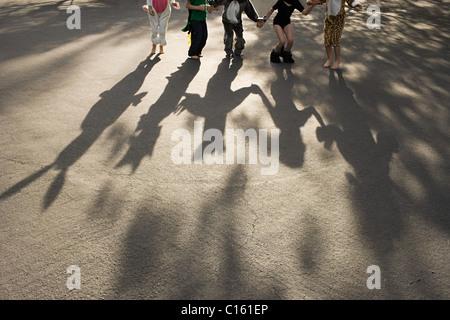 Cinq enfants déguisés se tenir la main, l'ombre de coulée Banque D'Images