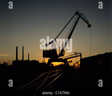 L'installation de manutention en vrac, rétro-éclairé, les crane et la voie raccordement par le coucher du soleil, Banque D'Images