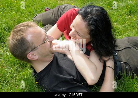 Jeune couple lying on grass Banque D'Images
