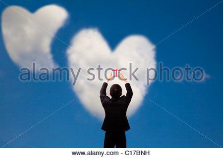Man holding gift et deux nuages coeur et l'amour Banque D'Images