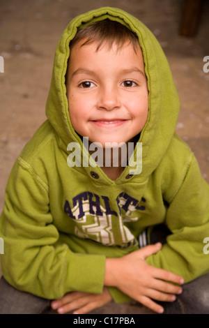 Jeune garçon portant un cavalier à capuchon vert Banque D'Images