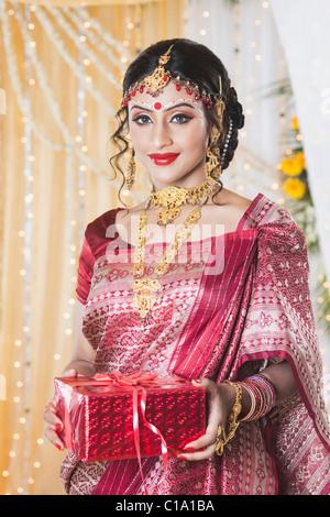 Portrait d'une mariée en robe traditionnelle Bengali holding un cadeau Banque D'Images