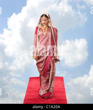 Robe mariée en bengali debout sur un tapis de nuages Banque D'Images