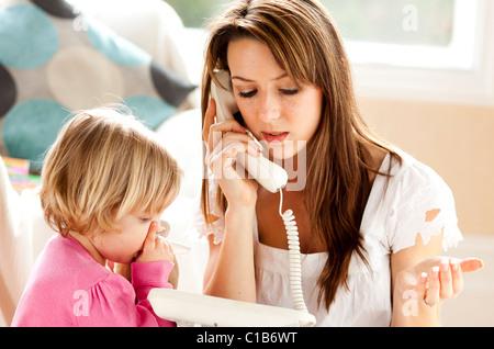 Woman on phone avec enfant en arrière-plan Banque D'Images