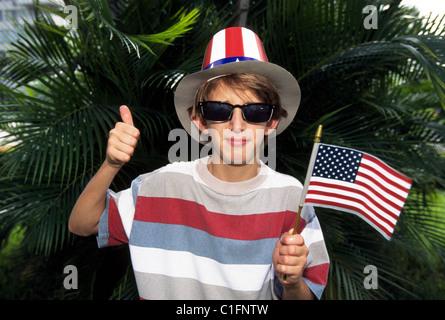Un garçon patriotique dans un oncle Sam hat vagues le drapeau américain lors d'une journée de l'indépendance (4 Banque D'Images