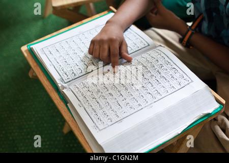 Jeune garçon lire le Coran. Little India, Singapour Banque D'Images