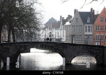 Cycliste sur Pont sur canal, matin d'hiver brumeux, Bruges, Belgique Banque D'Images