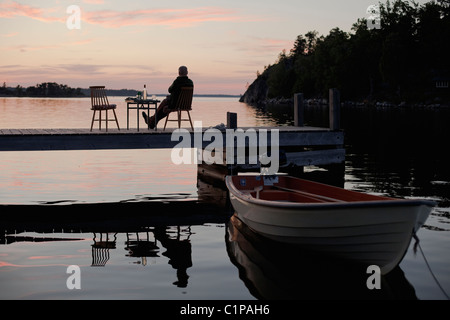 Silhouette of man sitting on pier Banque D'Images