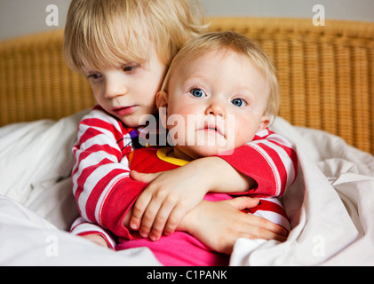 Garçon embrassant sœur on bed Banque D'Images