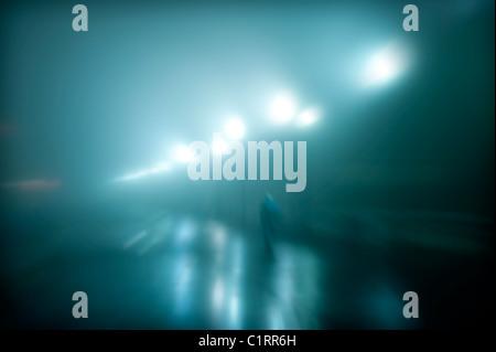 Mystérieux personnage marche sur une nuit de brouillard humide. Banque D'Images
