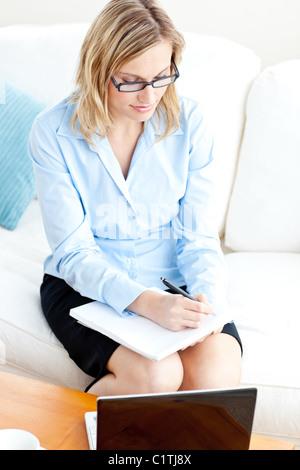 Young businesswoman wearing glasses écrit dans son calepin et en utilisant son ordinateur portable sur un canapé