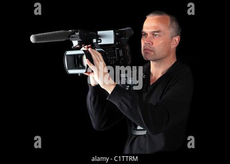 Vidéographe mâle monté son épaule points caméra vidéo et films dans la nuit Banque D'Images