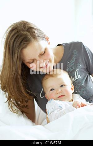 Portrait of a happy mother hugging son bébé tout en vous relaxant dans le lit Banque D'Images