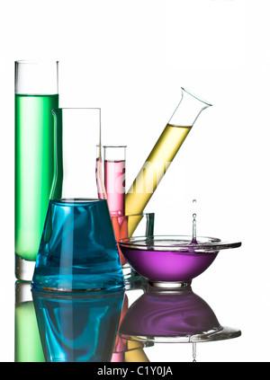 Verrerie de laboratoire avec des liquides colorés et congelé waterdrop, reflétée sur la surface blanche Banque D'Images