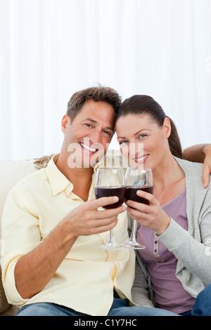 Quel beau couple drinking red wine sur le canapé Banque D'Images