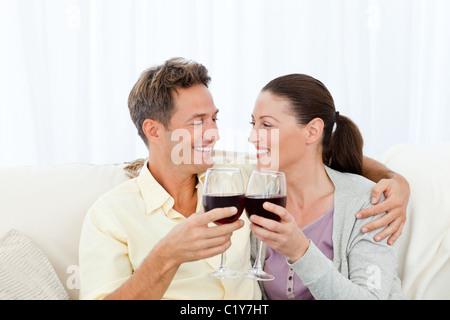 Deux passionnés de boire le vin rouge tout en vous relaxant sur le canapé Banque D'Images