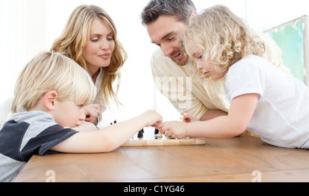 Famille en jouant aux échecs sur une table Banque D'Images