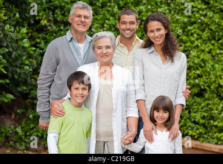 Portrait d'une famille heureuse regardant la caméra dans le jardin