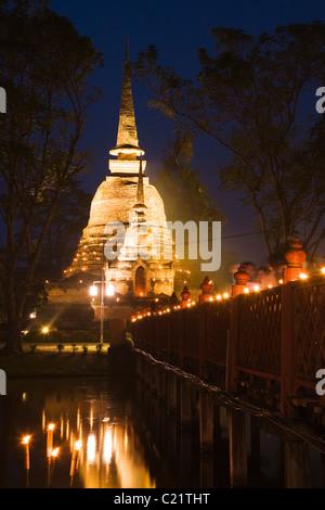 Un chedi du Wat Sa Si est illuminé par les lampes à pétrole pendant le festival de Loi Krathong. Sukhothai, Thaïlande Banque D'Images