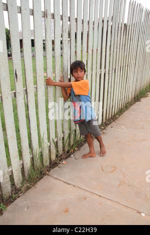 Jeune garçon debout à côté de l'Amérique latine fence Banque D'Images