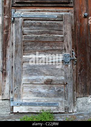 Ancienne en bois de porte de protection flétri avec les mauvaises herbes à l'avant Banque D'Images
