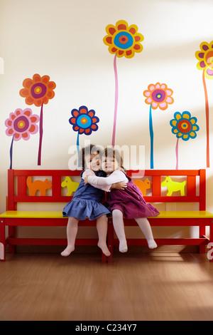 Blancs et Hispaniques d'âge préscolaire féminin assis sur un banc dans le jardin d'enfants, jouer et sourire. Banque D'Images