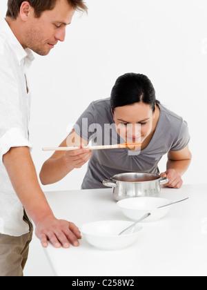 Cute woman tasting sa soupe avec son mari dans la cuisine Banque D'Images
