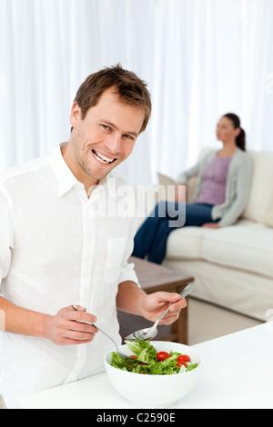 Homme heureux de préparer le déjeuner pendant que son amie se détendre Banque D'Images