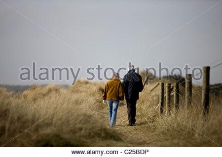 Un couple en train de marcher le long d'un chemin ensemble, vue arrière Banque D'Images