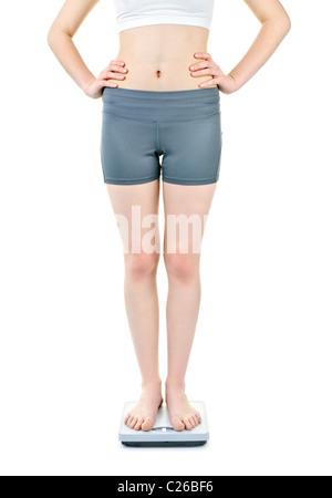 Santé de la jeune femme debout sur l'échelle de bain isolated on white Banque D'Images