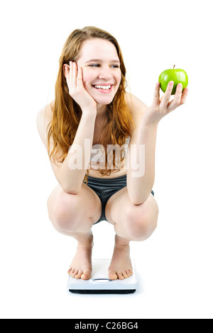Healthy happy young woman holding apple sur balance de salle isolated on white Banque D'Images