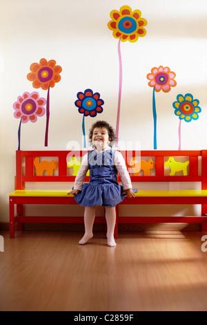 Portrait bambin assis sur un banc dans le jardin d'enfants et de sourire. La forme verticale, pleine longueur, vue Banque D'Images