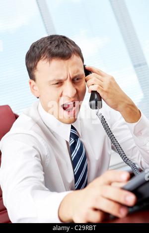 Un manager assis à table et criant dans le récepteur de téléphone Banque D'Images