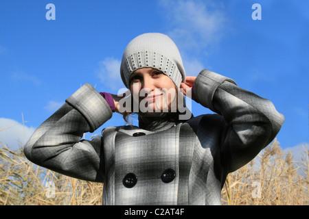 ... La jeune fille dans un manteau à carreaux contre le ciel bleu Banque  D Images 79daa28b685