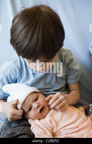 Jeune garçon toucher la joue d'enfant de bébé Banque D'Images