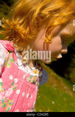 Jeune fille dans une tête rouge robe rose portant une chaîne Banque D'Images